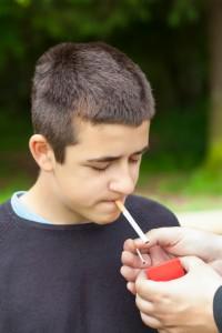Boy lighting up a cigarette